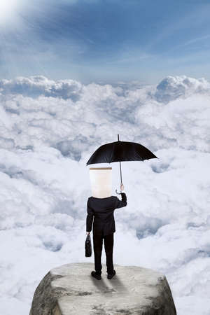 financial cliff: Rear view of businessman with cardboard head, standing on the mountain while holding umbrella and suitcase