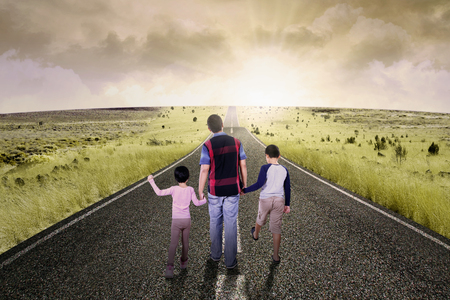 children holding hands: Image of two children walking  on the street with their father while holding hands