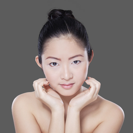 hair treatment: Closeup of chinese girl with black hair and beautiful skin after spa treatment, shot in the studio Stock Photo