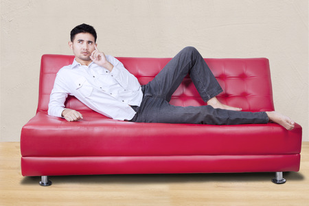people relax: Photo of young asian person relaxing while lying on the sofa while and thinking idea
