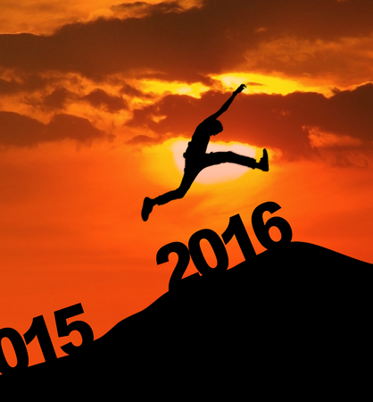 celebrate year: Image of silhouette man jumping over 2016 number to celebrate the new year. Shot at sunset time