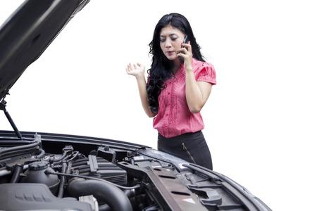 助けを求めたり、メカニックを呼ぶに電話で話している壊れた車を持つ若いアジア女性の肖像画
