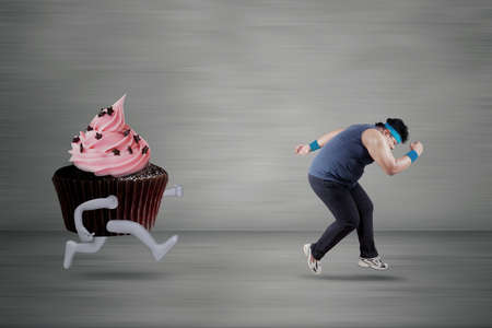 chased: Portrait of overweight person wearing sportswear and chased by a cupcake