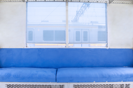 Image of empty seats and window with blue color inside commuter train Stock Photo