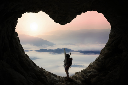 trekker: Silhouette of female backpacker with bag, standing inside cave shaped heart symbol while enjoying mountain view