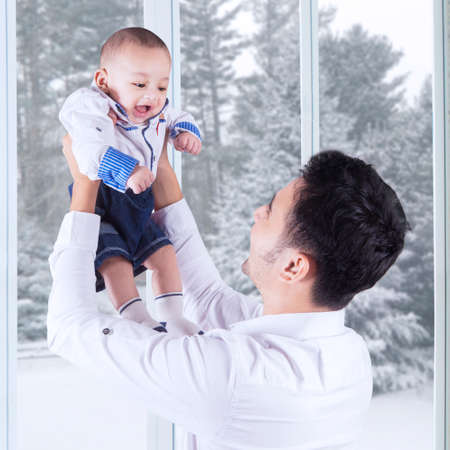 babies playing: Portrait of happy father lifting up his little son at home, shot with winter background on the window Stock Photo