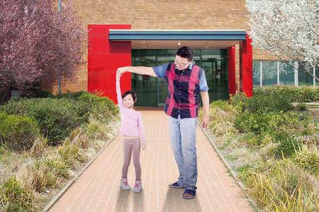 ni�os saliendo de la escuela: Imagen de la ni�a linda celebraci�n manos del padre y bailando delante de la escuela