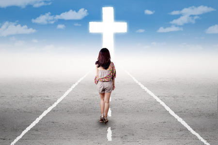 highway love: Young teenage girl walking alone on the road and follow the cross