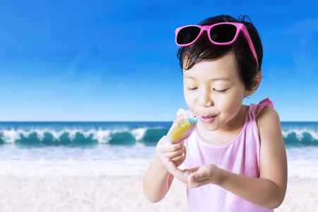 cute little girl smiling: Joyful little girl holding an melting ice cream while enjoying it on the beach