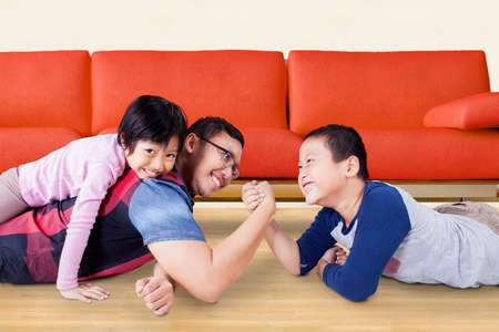 hispanic girl: Portrait of little boy with funny expression while arm wrestling with his father at home Stock Photo