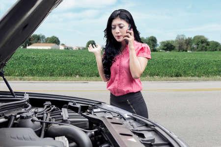 Image de jolie jeune femme avec voiture cassée, utilisant le téléphone mobile pour demander de l'aide sur la route Banque d'images