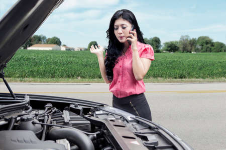 car breakdown: Image of young pretty woman with broken car, using mobile phone for asking help on the roadside