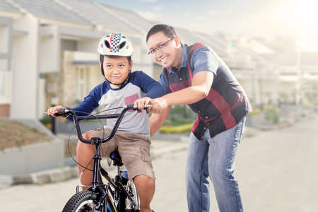 teach: Young dad training his son to ride a bike while holding the bike, shot on the road near the house