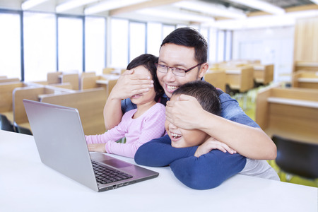 eyes closing: Portrait of young teacher closing the student eyes and prevent them to watch adult content on the laptop
