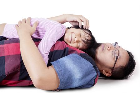 padre e hija: Imagen del feliz padre tendido en el suelo mientras abrazaba a su hija, aislado en fondo blanco Foto de archivo