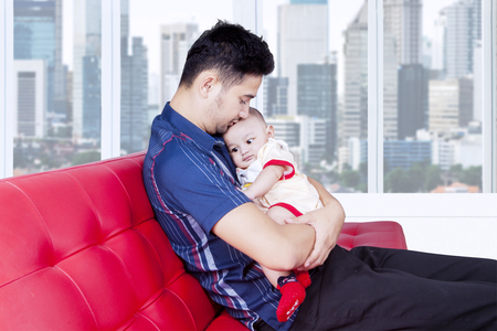 middle eastern families: Image of young man sitting on the sofa while take care his baby at home Stock Photo