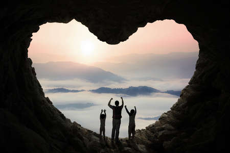 symbol: Silhouette of happy father and his children standing inside cave shaped heart symbol