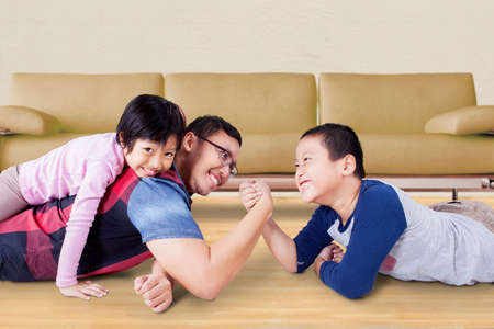 playful: Image of young father playing with his kids and arm wrestling with his son at home Stock Photo