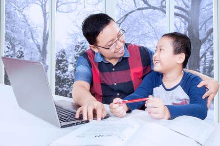 papa: Portrait de jeune père avec des vêtements décontractés parler avec son fils tout en le guidant à étudier avec un ordinateur portable et des livres à la maison Banque d'images