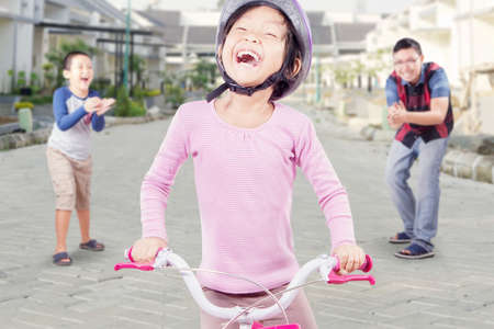 clapping hands: Portrait of happy little girl riding bicycle with her dad and brother clapping hands on the back