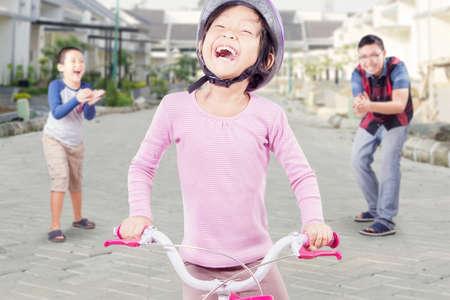 manos aplaudiendo: Retrato de la ni�a feliz que monta la bicicleta con su padre y hermano aplaudiendo las manos en la espalda Foto de archivo