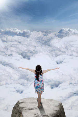 standing stones: Rear view of young girl standing on the rock at mountain peak while enjoying fresh air and outstretched hands
