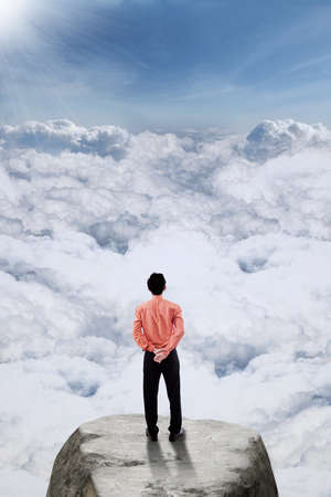 rise: Rear view of young businessman standing on the rock at mountain peak while looking at cloudscape