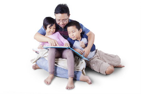 Portrait of happy family with two children and their father sitting on the floor while reading a story book