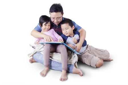 Portret van gelukkige gezin met twee kinderen en hun vader zittend op de vloer, terwijl het lezen van een verhaal boek Stockfoto