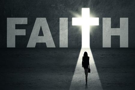christians: Silhouette of woman walking toward faith door Stock Photo