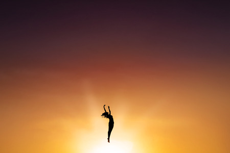 successful woman: Silhouette of female ballet dancer, dancing on the air at sunset time, shot outdoors Stock Photo