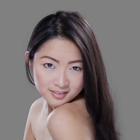beautiful black woman: Portrait of a young chinese woman with smooth skin after spa, looking and smiling at the camera in studio