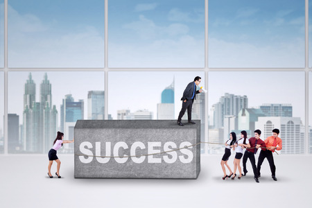 young entrepreneurs: Group of young entrepreneurs work together to move an obstacle with a text of success in office Stock Photo
