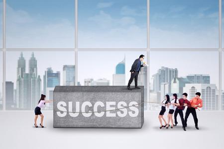 jovenes emprendedores: Grupo de jóvenes empresarios trabajando juntos para mover un obstáculo con un texto de éxito en la oficina