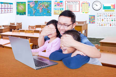 eyes closing: Photo of male teacher closing the students eyes and prohibit them watching adult content on the laptop