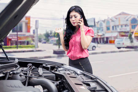 damaged vehicles: Portrait of pretty asian woman with broken car on the road side, asking help by phone