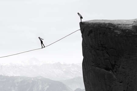 fear woman: Image of businesswoman taking risk and walking on the rope over the gap Stock Photo