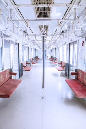 handrails: Photo of commuter trains room with empty seats and handrails