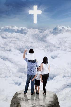 familia cristiana: Imagen de dos padres y sus niños que se colocan en el acantilado mirando un signo de la cruz en el cielo