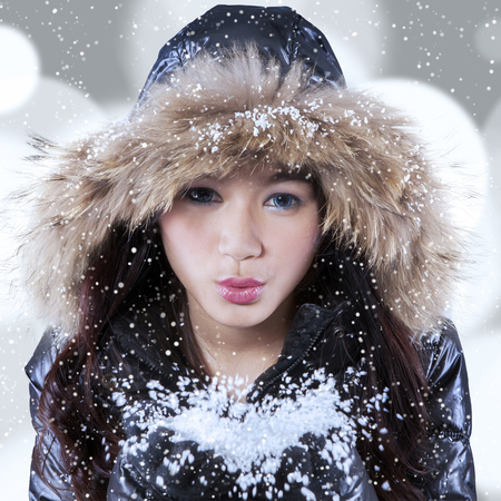 fur hood: Portrait of beautiful girl wearing winter clothing with fur hood, holding snow and blowing its