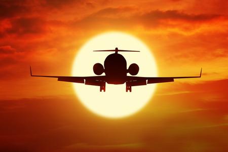 transportation: Silhouette d'avion volant sur le ciel avec une couleur orange au coucher du soleil