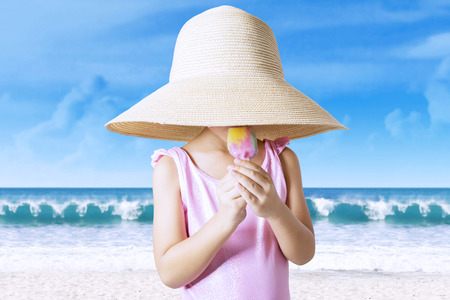 child swimsuit: Portrait of little child standing on the coast while wearing swimsuit and hat, enjoying ice cream