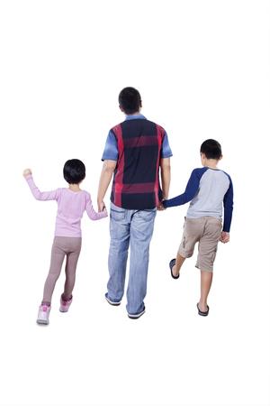 persona caminando: Vista trasera de un joven padre y sus niños de la mano en el estudio y caminando juntos Foto de archivo