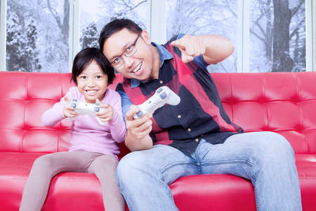 playstation: Portrait of cheerful father and his daughter playing playstation while sitting on the sofa at home Stock Photo