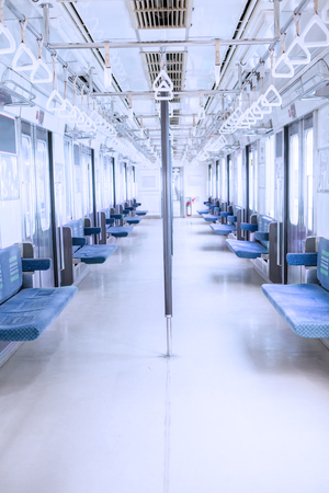 handrails: Image of empty corridor with seats and handrails inside commuter train Editorial
