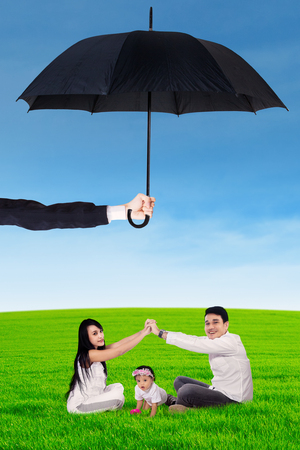 family life: Portrait of two young parents and their little daughter playing on the meadow under umbrella. Life and family insurance concept