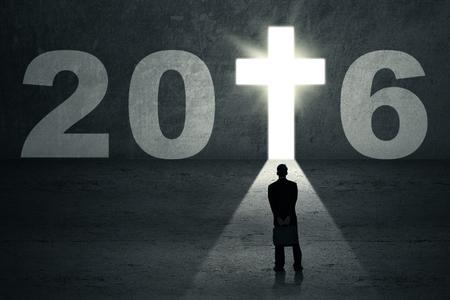 cruz de jesus: Empresario joven mirando a una puerta en forma de un símbolo de la cruz y los números de 2016