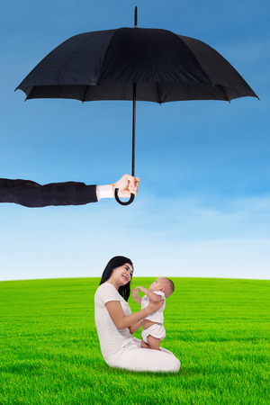 protect family: Portrait of young happy mother playing with her daughter on the meadow under umbrella. Life and family insurance concept Stock Photo