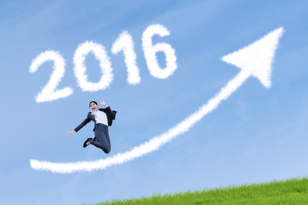 year increase: Image of happy businesswoman jumping on the meadow with cloud shaped numbers 2016 and upward arrow Stock Photo