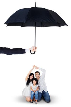 proteccion: Retrato de los padres alegres y su hija sentada en el estudio bajo el paraguas. Seguro de vida y el concepto de familia